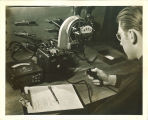 Engineering student working with electrical meters and gauges in engineering laboratory, The University of Iowa, 1939
