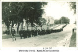 Cadet leading commencement procession down Washington St. with MacLean Hall, left, and Schaeffer Hall in background, The University of Iowa, 1910s