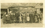 Men in military uniforms and women and children posing in front of a bus, Early, Iowa, 1910s