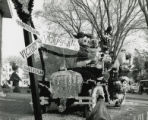 Homecoming law display of Disney characters and Cy riding in a jalopy in Victoryland, 1961