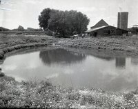Two unidentified men stand with horses beside a barn in back of a pond
