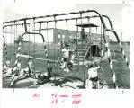 Children playing on Hawkeye Drive Apartments playground, the University of Iowa, 1966