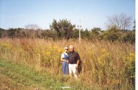 Man and woman standing near Big Bluestem and Golden Rod