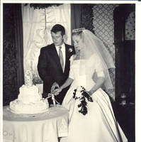 Frindy and John, Sr., look at cake while cutting it, in dining room