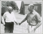 Two men talking by a low wire fence