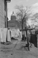 Woman hanging clothes at her home near the statehouse.