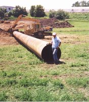 Unidentified man standing next to large pipe