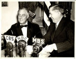 Vice president Henry A. Wallace with President Franklin Roosevelt in front of radio microphones,…