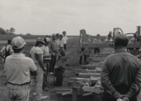 Farmers Inspect a Buffalo No-till Planter in a Field.