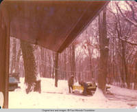 Two unknown men working on snow plow