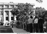 Students in line at south entrance of Macbride Hall on Pentacrest, Iowa City, Iowa, 1956
