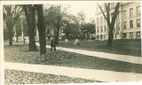 Man raking leaves on the Pentacrest in front of the Old Capitol, The University of Iowa, between 1920 and 1924
