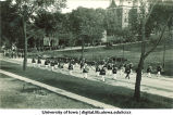 Marching band leading procession on Madison St. past Pentacrest, The University of Iowa, October 1, 1923