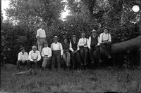 UP388 Nine men on a log with E.W. Hanson standing