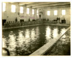 Men sitting around the swimming pool in State Gymnasium