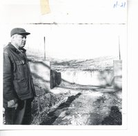 Verne Scheckel with erosion control structure in background