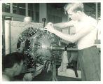 Engineering students working on airplane engine, The University of Iowa, 1950s