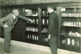 Men looking at a cabinet of chemistry compounds, The University of Iowa, 1930s