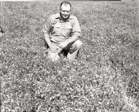 Man in White Overalls Kneels in Tall Grass