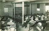 Geology professor lecturing students in front of blackboard, The University of Iowa, 1920s