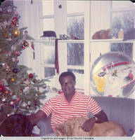 Ainsley Benard sitting on couch at Christmas with Victoria in his lap and Sadie at his side