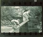 Boys climbing up a makeshift slide, The University of Iowa, May 10, 1941