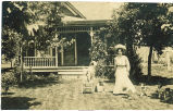 Mary White with dogs in front of house, Maynard, Iowa, 1909