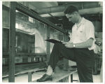 Engineering student recording data from water experiment in engineering laboratory, The University of Iowa, 1939