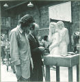 Instructor inspecting student's sculpture, The University of Iowa, 1940s