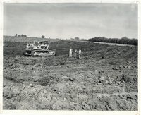 Men in bulldozed field