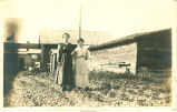 Mother and daughter by farm buildings, Iowa?, 1910s