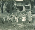Children and teachers playing game outdoors, The University of Iowa, 1920s