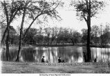 Men seated on banks of City Park pond, Iowa City, Iowa, between 1915 and 1920