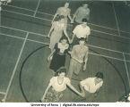 Couples walking across gymnasium hand in hand, The University of Iowa, 1940s