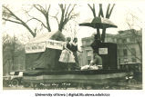 Men in women's attire on float in Mecca Day parade, The University of Iowa, 1920
