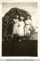Three women by lilac bush