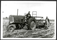 Men Pose with a Tractor in a Field