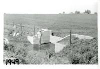 Tom Lewis standing next to a weir notch, 1949