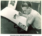 Artist Frank Dorsay designing war poster at War Art Workshop, The University of Iowa, 1942-43