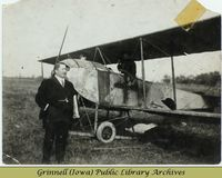 Man in front of biplane, Billy Robinson in cockpit
