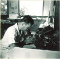Pharmacy student looking into a microscope, The University of Iowa, 1940s