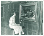 Woman examining painting in the Iowa Memorial Union, the University of Iowa, 1950s?