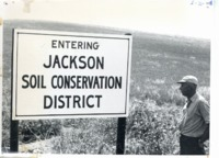 Harold Wilms stands before Jackson County soil conservation district sign
