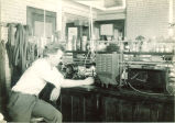 Student working with scientific equipment, The University of Iowa, 1930s?
