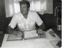 Fred Hainline Reads Material in Notebook