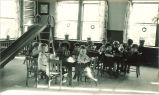 Children seated at tables in playroom, The University of Iowa, 1920s