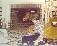 John, Jr. and corgy playing cards in front of fire place