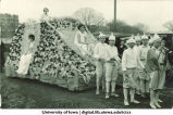 Boys preceding a parade float with seated women, The University of Iowa, 1920