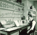 Man working with vials and chemistry equipment, The University of Iowa, 1930s