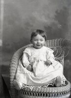 Infant smiling in white dress, seated in wicker chair